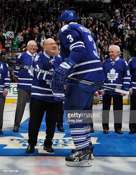 Toronto Maple Leafs Alumnus Johnny Bower shakes hands with Dion Phaneuf of the Toronto Maple Leafs prior to NHL game action between the Toronto Maple...