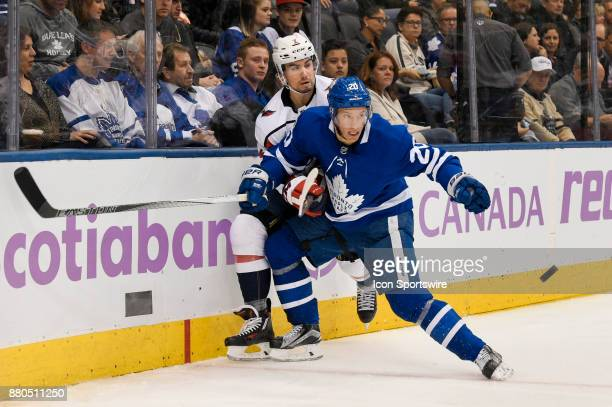 Toronto Maple Leafs Center Dominic Moore and Washington Capitals Defenceman Matt Niskanen fight for the puck behind the net during the NHL regular...