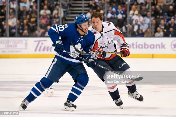 Toronto Maple Leafs Center Dominic Moore hits Washington Capitals Right Wing Alex Chiasson who lost his helmet during the NHL regular season hockey...