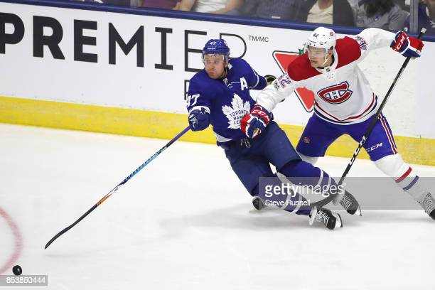 TORONTO ON SEPTEMBER 25 Toronto Maple Leafs center Leo Komarov loses an edge as he and Montreal Canadiens center Byron Froese go after a loose puck...
