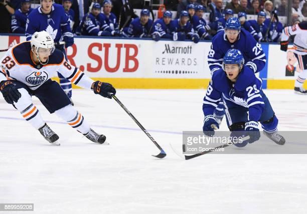 Toronto Maple Leafs center William Nylander battles for a puck with Edmonton Oilers defenseman Matt Benning during the third period in a game between...