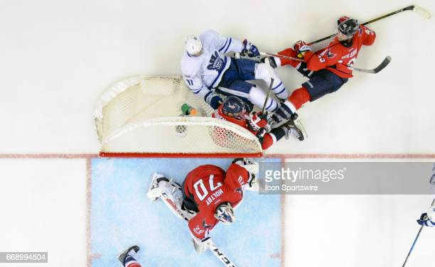 Toronto Maple Leafs center Zach Hyman goes into the net behind Washington Capitals goalie Braden Holtby with defenseman Matt Niskanen and right wing...