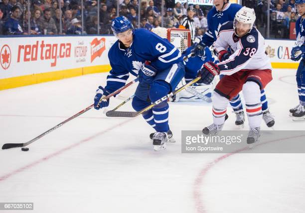 Toronto Maple Leafs defenseman Connor Carrick battles for a puck with Columbus Blue Jackets center Boone Jenner during the third period in a game on...