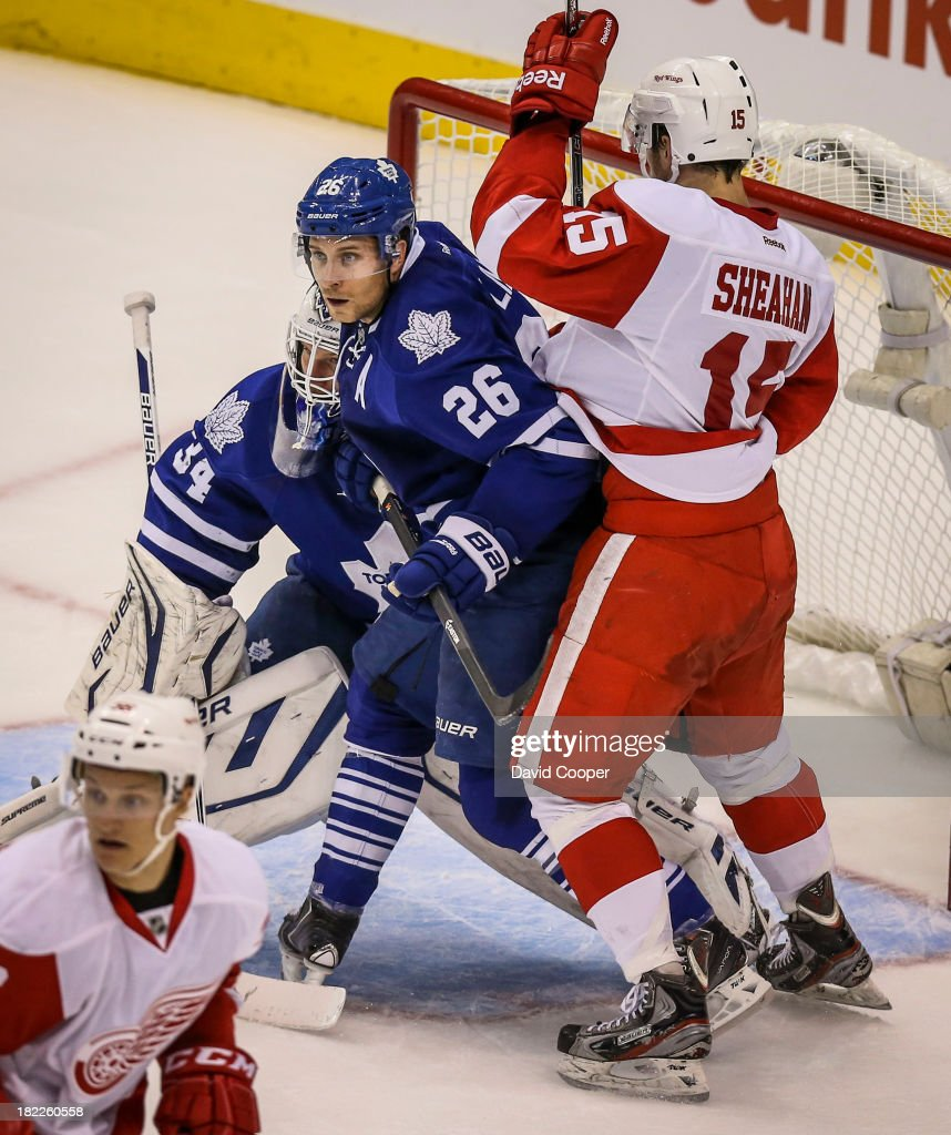 TORONTO, ON- SEPTEMBER 28 - Toronto Maple Leafs defenseman John-Michael Liles (26) tries to clear Detroit Red Wings center Riley Sheahan (15) from in front of Toronto Maple Leafs goalie James Reimer (34) as the Leafs beat the Red Wings 3-1 at the Air Canada Centre in Toronto, September 28, 2013.