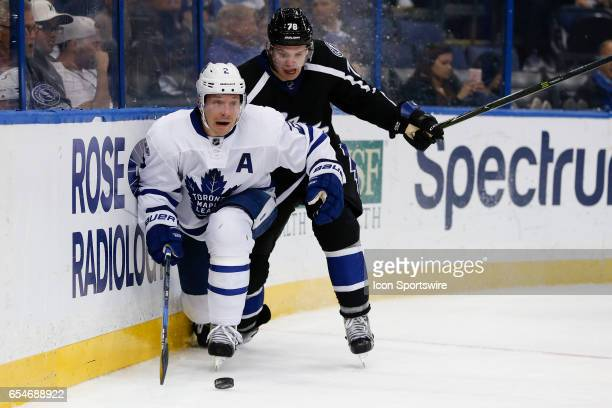 Toronto Maple Leafs defenseman Matt Hunwick and Tampa Bay Lightning center Byron Froese battle for the puck in the 3rd period of the NHL game between...