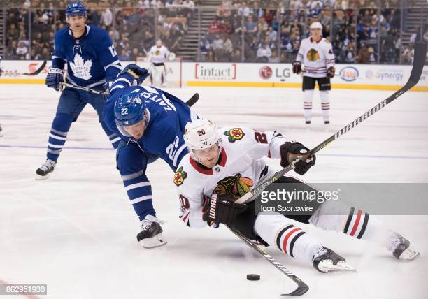 Toronto Maple Leafs defenseman Nikita Zaitsev battles for a puck with Chicago Blackhawks left wing Brandon Saad in the third period during the...