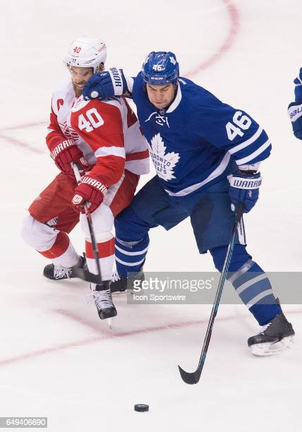 Toronto Maple Leafs defenseman Roman Polak battles for a puck with Detroit Red Wings left wing Henrik Zetterberg during the third period in a game at...
