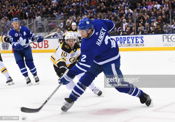 Toronto Maple Leafs defenseman Ron Hainsey clears a puck as Boston Bruins left wing Anders Bjork tries to check in the second period during a game...