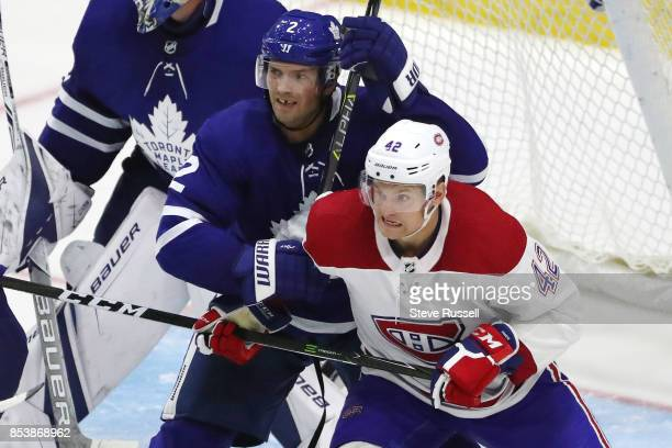TORONTO ON SEPTEMBER 25 Toronto Maple Leafs defenseman Ron Hainsey clears Montreal Canadiens center Byron Froese from the front of the net as the...