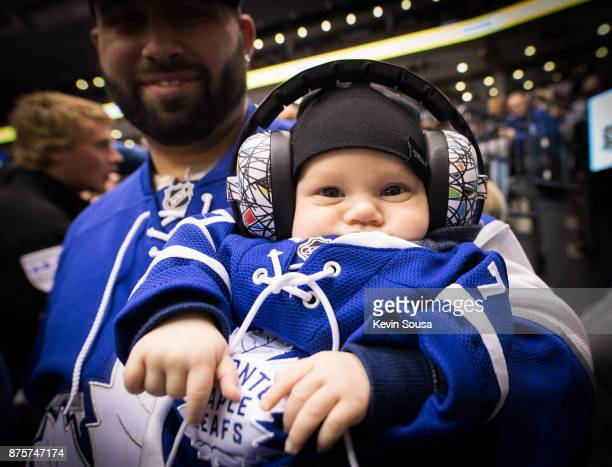 Toronto Maple Leafs fan holds his new born son at an NHL game against the New Jersey Devils during the third period at the Air Canada Centre on...