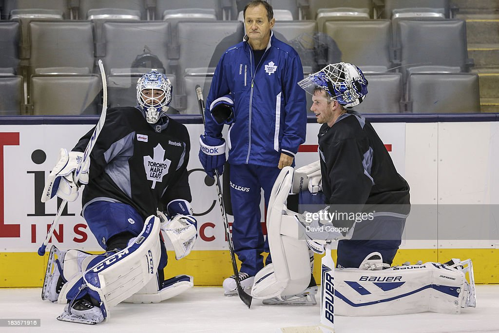 TORONTO, ON- OCTOBER 7 - Toronto Maple Leafs goalie <a gi-track='captionPersonalityLinkClicked' href=/galleries/search?phrase=Jonathan+Bernier&family=editorial&specificpeople=540491 ng-click='$event.stopPropagation()'>Jonathan Bernier</a> (45), Goaltending coach Piero Greco, and goalie James Reimer (34) talks near the side boards during practice at the Air Canada Centre in Toronto, October 7, 2013.