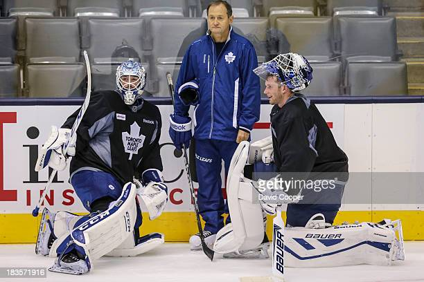 TORONTO ON OCTOBER 7 Toronto Maple Leafs goalie Jonathan Bernier Goaltending coach Piero Greco and goalie James Reimer talks near the side boards...