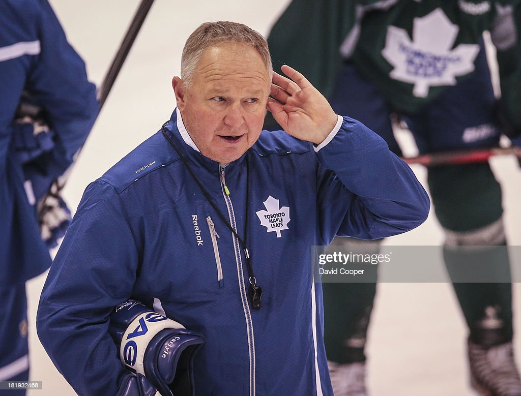 TORONTO, ON- SEPTEMBER 26 - Toronto Maple Leafs head coach <a gi-track='captionPersonalityLinkClicked' href=/galleries/search?phrase=Randy+Carlyle+-+Ice+Hockey+Coach&family=editorial&specificpeople=679108 ng-click='$event.stopPropagation()'>Randy Carlyle</a> tries to hear a player during practice at the MasterCard Centre for Hockey Excellence in Toronto, September 26, 2013.