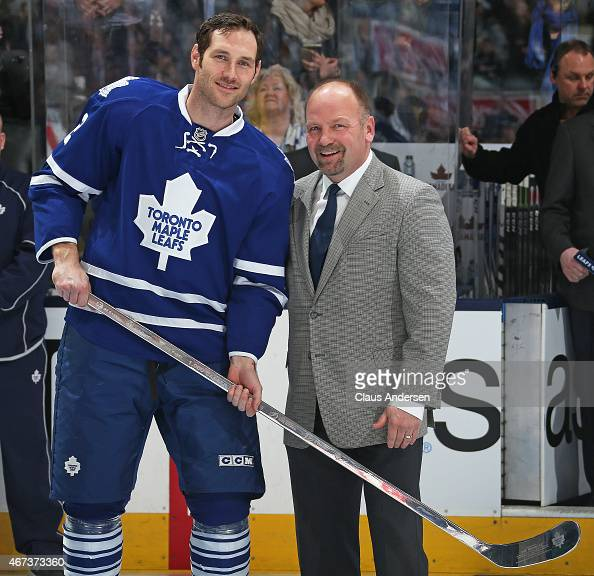 Toronto Maple Leafs legend Wendel Clark presents Eric Brewer of the Leafs a silver stick in honour of Brewer's 1000th NHL game prior to play against...