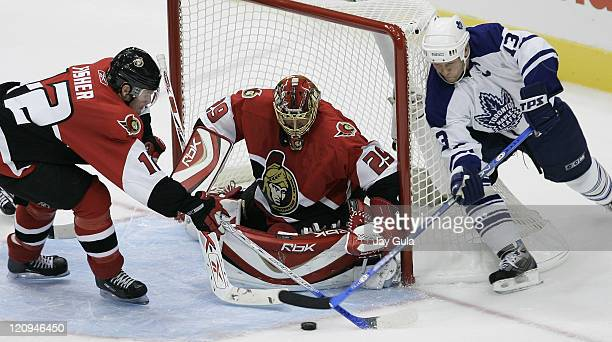 Toronto Maple Leafs Mats Sundin can't get the puck past goaltender Martin Gerber of the Ottawa Senators as Mike Fisher trys to help out in the NHL...