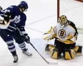 Toronto Maple Leafs Nik Antropov looks down for the puck which glanced off his skate and went into the net behind Boston goaltender Tim Thomas during...