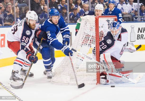Toronto Maple Leafs right wing Connor Brown skates behind Columbus Blue Jackets goalie Joonas Korpisalo as Columbus Blue Jackets defenseman David...
