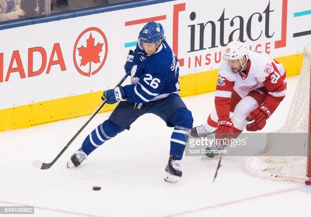 Toronto Maple Leafs right wing Nikita Soshnikov battles for a puck with Detroit Red Wings left wing Drew Miller during the third period in a game at...
