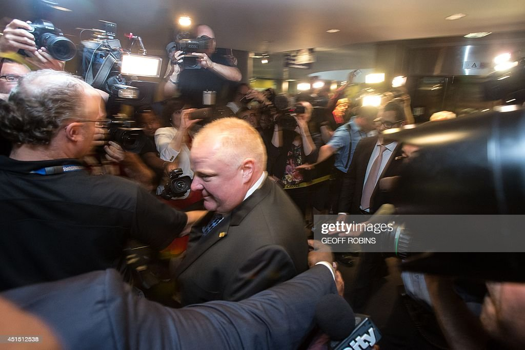 Toronto Mayor Rob Ford arrives at his office at city hall in Toronto on June 30, 2014 amid a crush of cameras. The crack-smoking mayor Rob Ford returned to work more popular than ever after a stint in rehab for his internationally publicized alcohol and drug abuse. AFP PHOTO/GEOFF ROBINS