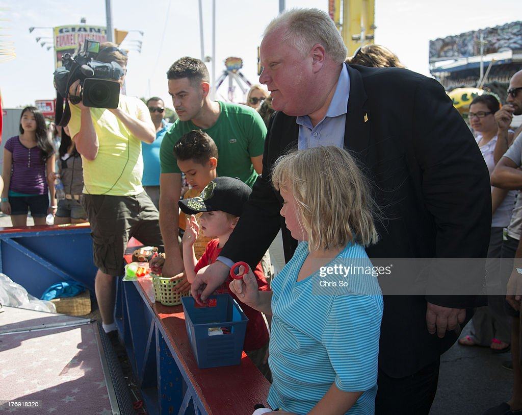 Toronto, ON - AUGUST 18 - Toronto Mayor Rob Ford tries his luck with the bottle ring toss with his children Stephanie and Dougie after the Mayors radio show. The Ford brothers had their weekly Newstalk 1010 radio show just inside the Prince's Gates at the CNE then went to check out the midway after the show.