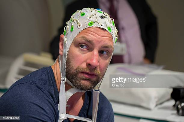 Toronto ON MAY 26 2014 Former NHL player Bryan Muir wears EEG cap prior to being placed into an MRI scanner The covering has 64 sensors which measure...