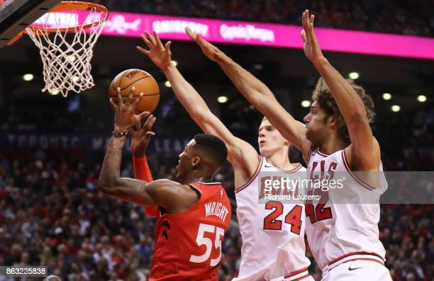 Toronto ON OCTOBER 19 In first half action Toronto Raptors guard Delon Wright drives to the hoop around Chicago Bulls forward Lauri Markkanen and...