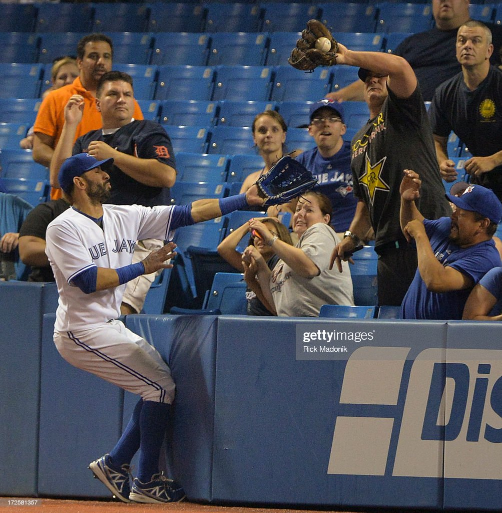 Toronto, Ontario - JULY 3 - Jays right fielder Jose Bautista probably could have made an out on the play if it weren't for the fan with a glove who snagged the ball. Toronto Blue Jays versus Detroit Tigers in Major League Baseball action at Rogers Centre, on Wednesday, July 3, 2013. Jays lose 6-2.