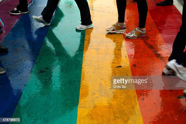 Toronto Ontario JUNE 27 2015 The rainbow painted crosswalks on Church Street reflect the feet of passersby after heavy rain Participants in the...