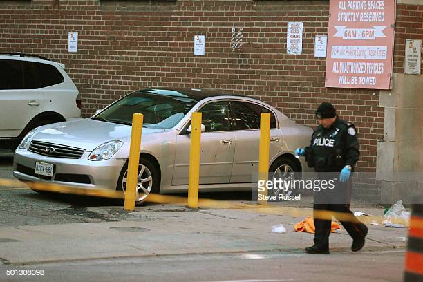 Toronto police officer walks by a car showing bullet holes near King and Peter Street in Toronto December 11 2015