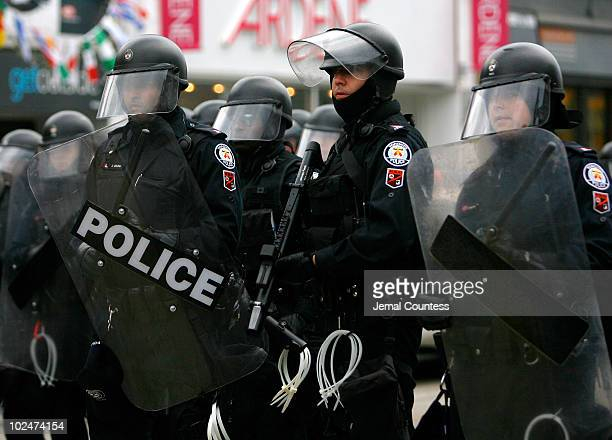 Toronto police officers take up positions as they face off with protestors during a protest at the corner of Queen street and Spidina avenue on June...