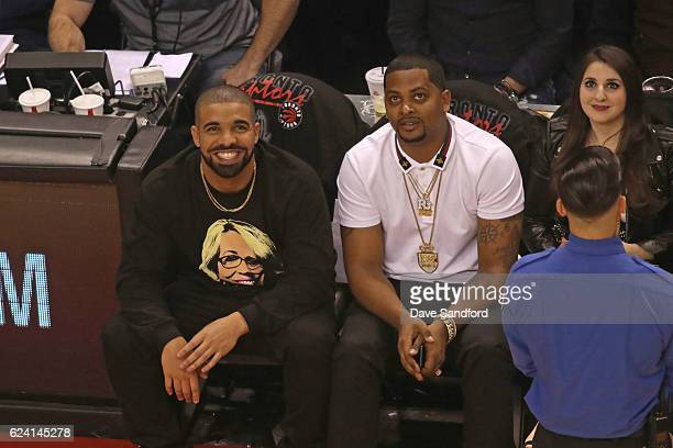 Toronto Raptors Ambassador and Performer Drake watches as the Golden State Warriors play against Toronto Raptors during their game at Air Canada...