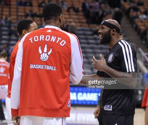 Toronto Raptors Amir Johnson and DeMar DeRozan spend a minute or two with former Raptor and now Brooklyn Nets Reggie Evans before the game at the ACC...