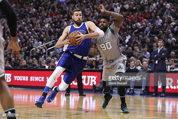 TORONTO ON JANUARY 10 Toronto Raptors center Jonas Valanciunas drives past Boston Celtics forward Amir Johnson as the Toronto Raptors wearing their...