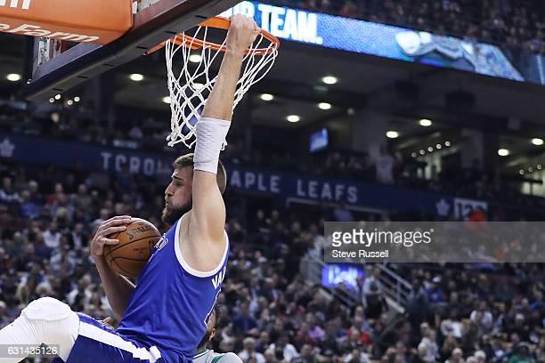 TORONTO ON JANUARY 10 Toronto Raptors center Jonas Valanciunas holds onto the ball and the rim after being fouled as the Toronto Raptors wearing...