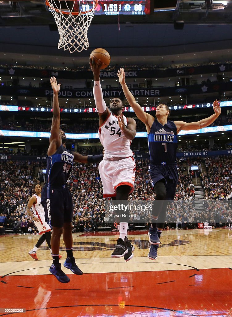 TORONTO, ON- MARCH 13 - Toronto Raptors forward Patrick Patterson (54) drives the lane between Harrison Barnes and Dwight Powell as the Toronto Raptors beat the Dallas Mavericks 100-78 at the Air Canada Centre in Toronto. March 13, 2017.