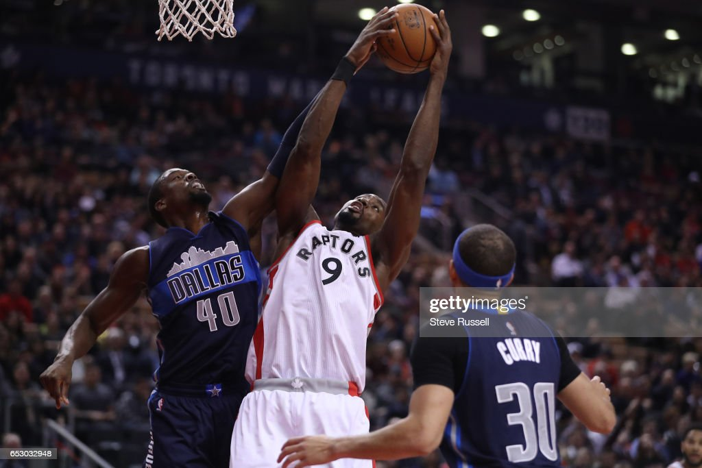 TORONTO, ON- MARCH 13 - Toronto Raptors forward Serge Ibaka (9) hauls in a rebound against Dallas Mavericks forward Harrison Barnes (40) as the Toronto Raptors play the Dallas Mavericks at the Air Canada Centre in Toronto. March 13, 2017.