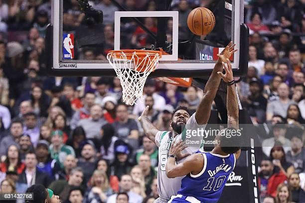 TORONTO ON JANUARY 10 Toronto Raptors guard DeMar DeRozan gets the ball over Boston Celtics forward Amir Johnson as the Toronto Raptors wearing their...