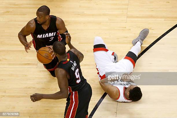 Toronto Raptors guard DeMar DeRozan grabs his hand in some discomfort as Miami Heat guard Dwyane Wade takes the ball and heads to the other end for a...