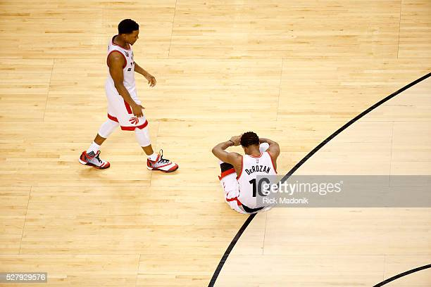 Toronto Raptors guard Kyle Lowry comes to comfort Toronto Raptors guard DeMar DeRozan who sits holding his hand after losing the ball with seconds...