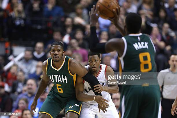 TORONTO ON JANUARY 5 Toronto Raptors guard Kyle Lowry keeps Utah Jazz forward Joe Johnson close by as Shelvin Mack looks for someone to pass to as...