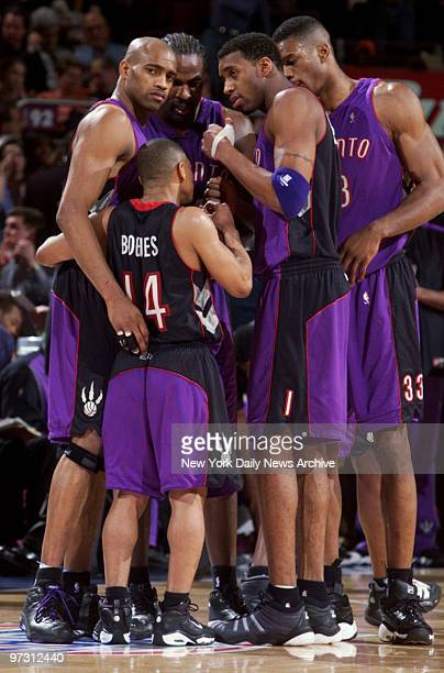 Toronto Raptors' Muggsy Bogues is dwarfed by his teammates as they talk strategy during game two of the first round of the NBA playoffs against the...
