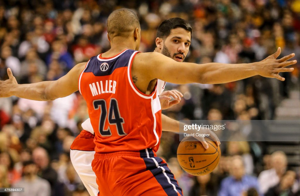 TORONTO, ON- FEBRUARY 27 - Toronto Raptors point guard Greivis Vasquez (21) looks to pass while being guarded by Washington Wizards point guard Andre Miller (24) during the game between the Toronto Raptors and the Washington Wizards Air Canada Centre February 27, 2014.