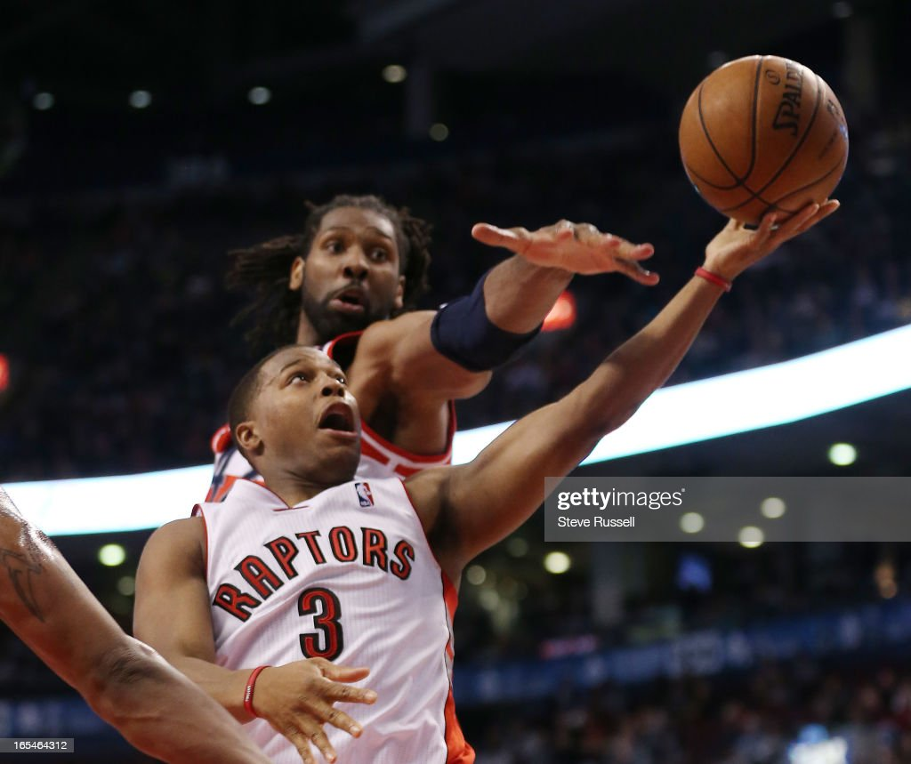 Toronto Raptors point guard Kyle Lowry (3) tries to sneak under Nene in first half action as the Toronto Raptors play the Washington Wizards to at the Air Canada Centre in Toronto.