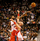 TORONTO ON FEBRUARY 27 Toronto Raptors power forward Amir Johnson swats the ball away from Washington Wizards center Marcin Gortat during the game...