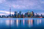 Spectacular View of Downtown Toronto under Cloudy Sky at Dusk with Lights Reflecting in Water. Ontario, Canada.