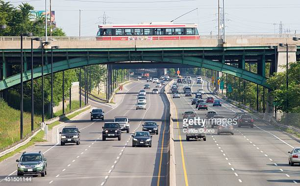 Toronto Transit Commission streetcar heads eastbound on Gerrard Street East while below motorist commute on the Don Valley Parkway in Toronto on June...