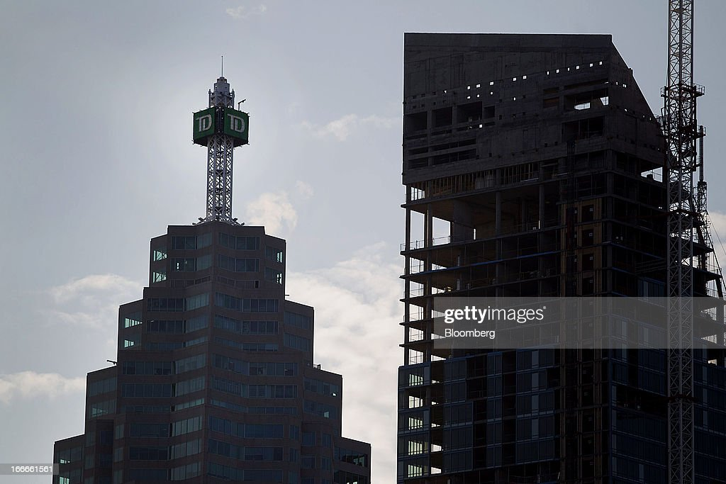 Toronto-Dominion Bank's TD Canada Trust Tower stands next to a building under construction in Toronto, Ontario, Canada, on Sunday, April 14, 2013. The Canadian dollar fluctuated against its U.S. counterpart amid speculation the economy is slowing after an unexpected jobs loss last month. Photographer: Pawel Dwulit/Bloomberg via Getty Images