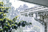 Drenching downpour rain storm water is overflowing off the tile shingle roof - streaming, rushing and splashing out over the overhanging eaves trough aluminum roof gutter system on a suburban resident