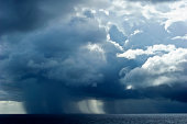 A torrential tropical rainstorm descends over the ocean surface.