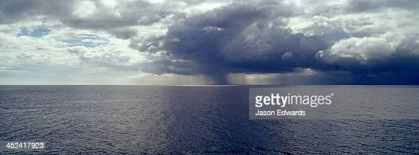 A torrential tropical rainstorm descends over the ocean surface.